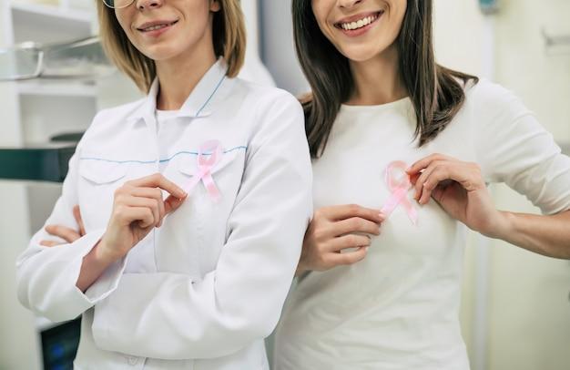 Две женщины демонстрируют медицинскую липкую ленту, посвященную раку, для защиты женской груди и профилактики рака