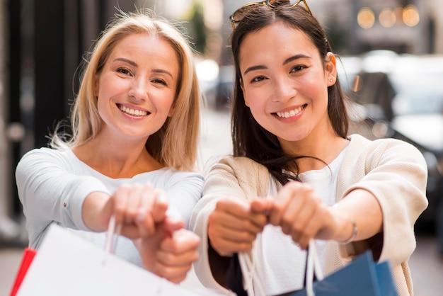 쇼핑을 골라서 쇼핑 후 defocused 쇼핑백을 보여주는 두 여자