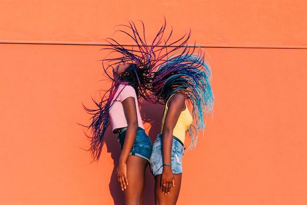 Two women sisters dancing movng hair outdoor
