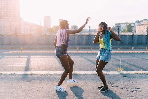 Two women sisters outdoor listening music dancing