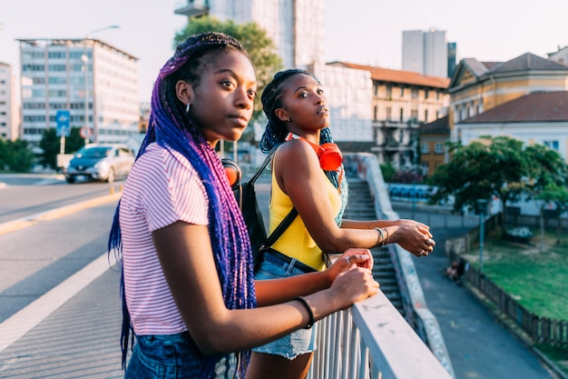Two women sisters posing outdoor city looking away