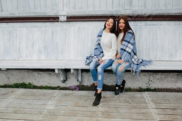 Две женщины сидят на скамейке в парке и позируют