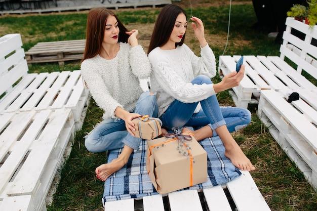 두 명의 여성이 야외 벤치에 앉아 스마트 폰 선물을 촬영합니다.