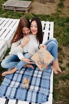 Две женщины сидят на скамейке на улице и снимают подарки для смартфона