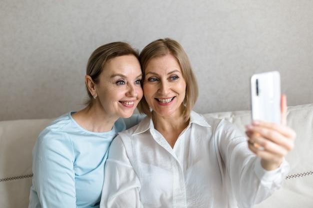Две женщины сидят на диване и делают селфи по телефону во время разговора