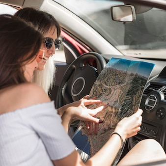Two women sitting in car looking at map