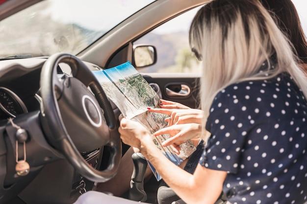 Due donne che si siedono in macchina che indica sulla mappa