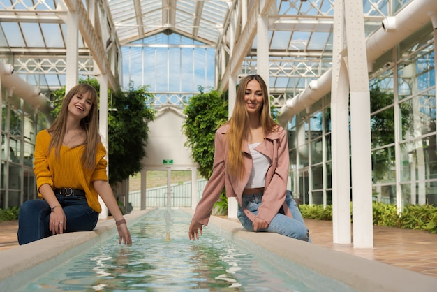 Two women sitting on the edge of a fountain with water inside a bright greenhouse