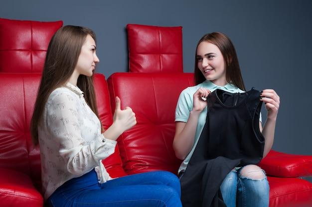 Две женщины сидят на диване и примеряют платья