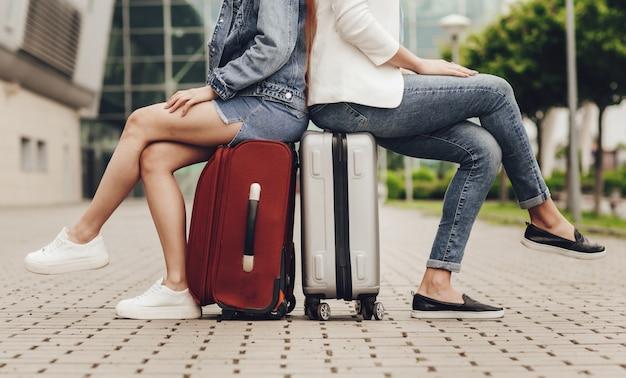 フライトを待っているスーツケースに座っている2人の女性。ジーンズとスカートのグレーと赤のスーツケースにかわいい女性の足のクローズアップ。友達と一緒に旅行。旅行を待っている観光客