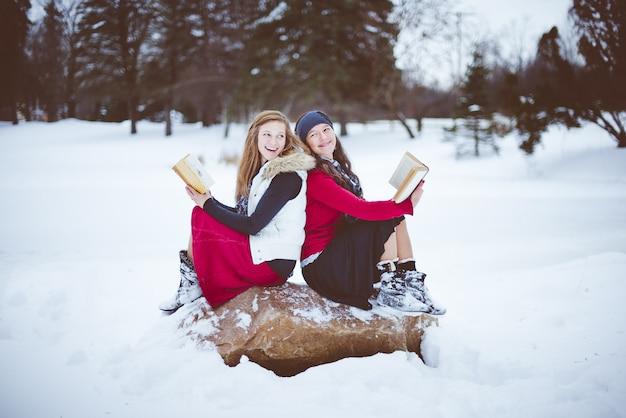 Due donne sedute sulla roccia schiena contro schiena durante la lettura