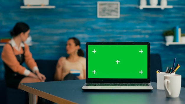 Two women sitting together on sofa in background talking about internet technology. in front on desk table standing isolated laptop computer with mock up green screen chroma key in office home