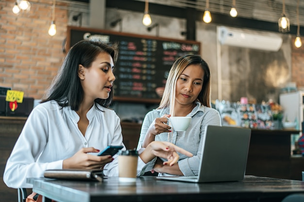 Two women sitting and working with a laptop in a coffee shop