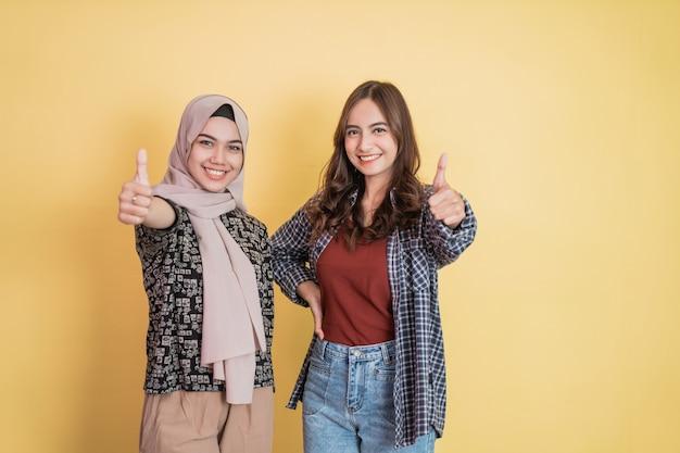 Две женщины улыбаются в камеру с большим пальцем вверх жестом с copyspace рядом