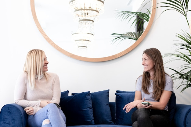 Two women smiling in a waiting room