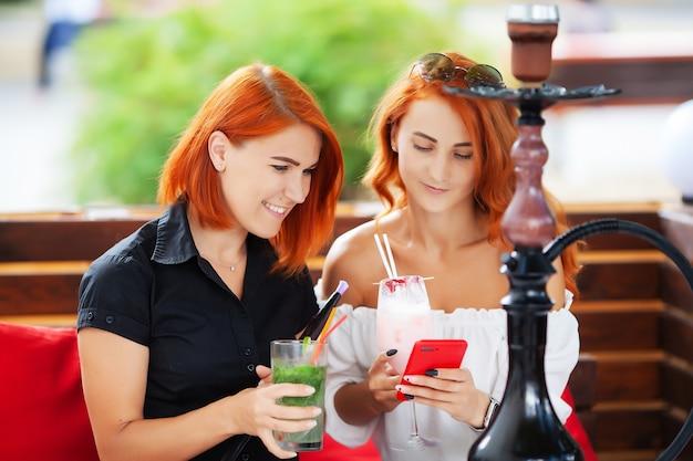 두 명의 여성이 물 담뱃대를 피우고 길거리 카페에서 칵테일을 즐깁니다.