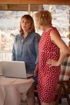 두 명의 여성이 노트북을 들고 테이블 근처에 서서 문제에 대한 해결책을 논의합니다
