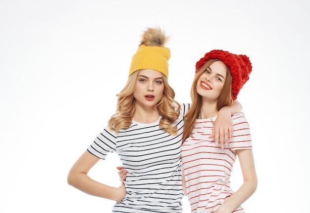 2人の女性がモダンな服の友情の明るい背景でファッショナブルな隣に立っています