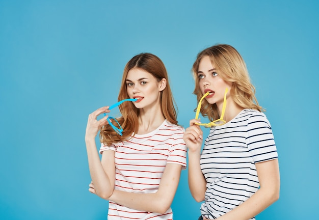 2人の女性が縞模様のtシャツのファッションの魅力的な外観の青い背景に並んで立っています