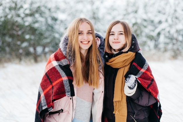 Two women standing in winter forest