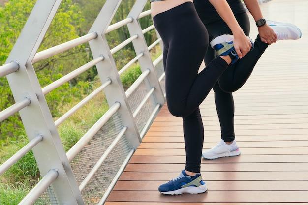 달리기 전에 다리 위에서 스트레칭을 하는 두 여성.