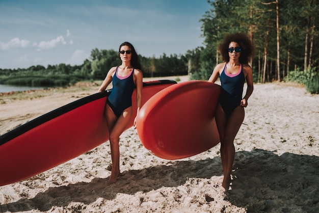 Two women surfers standing on beach in swimsuits.