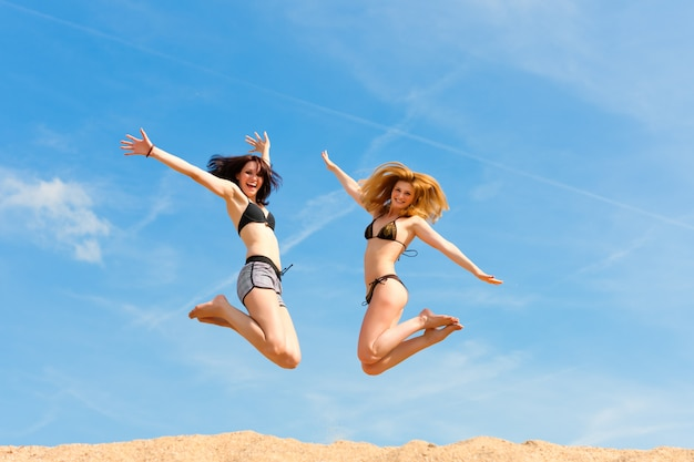 Two women in swimwear happily jumping up above the sandy beach