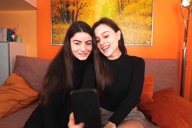 ソファで自分撮りをしている2人の女性