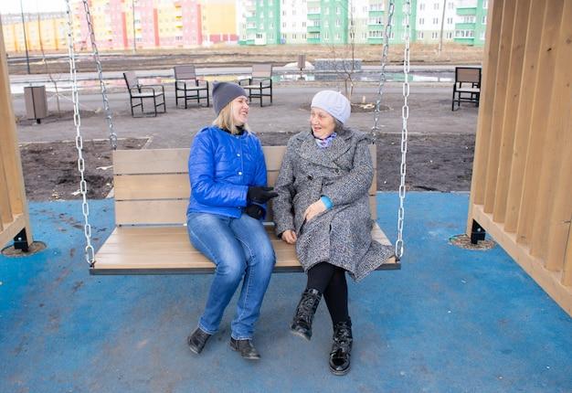 두 명의 여성이 이야기하고 웃는 세대 딸과 노모의 연결