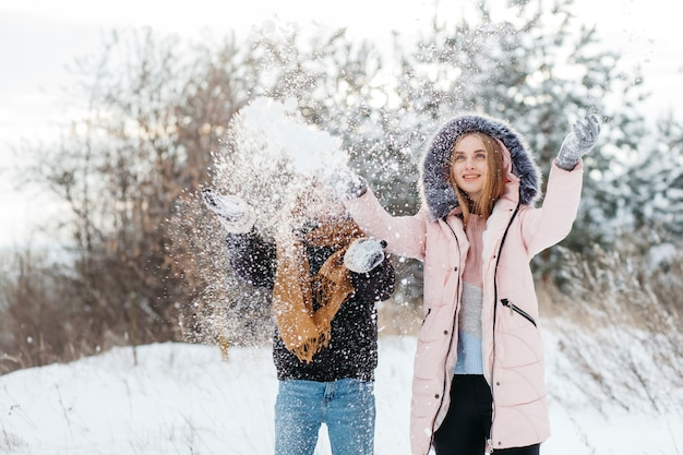 Two women throwing snow in air