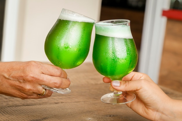 Two women toasting st. patricks day, on wooden table.