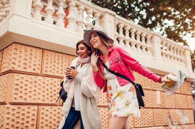 Две женщины-туристы с удовольствием едут на экскурсию по карте одессы. счастливые друзья путешественники смеются во время прогулки