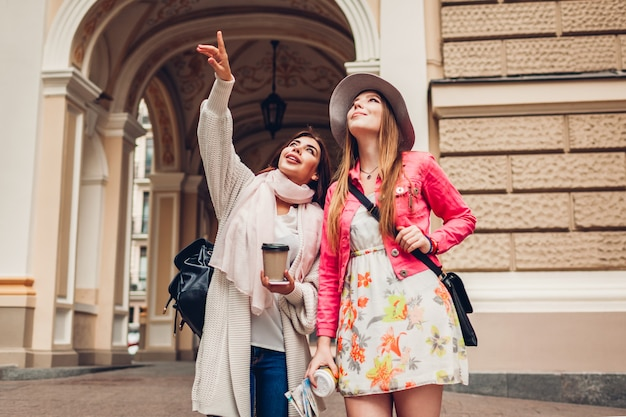 Two women tourists talking while going sightseeing in odessa. happy friends travelers pointing up