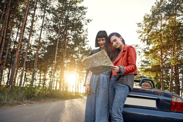 Two women trying to find the way on map near cabriolet