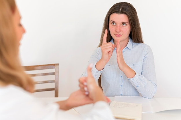 Two women using sign language to converse at table