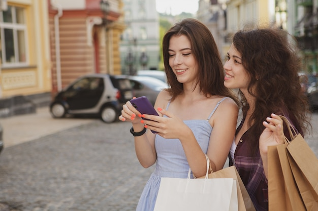 Two women using smart phone, walking in the city after shopping together