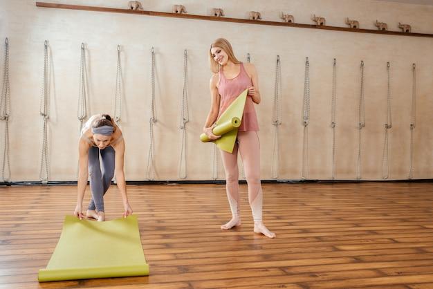 Две женщины в спортивной одежде держат коврики для йоги, стоя в спортивной студии
