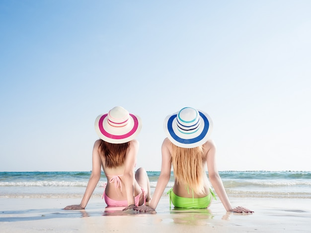 Two women wearing bikinis on the beach, sundeck seating. relaxing on the beach
