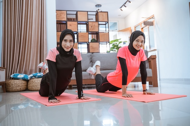 Two women wearing hijab sportswear smile while doing push up movements together at home