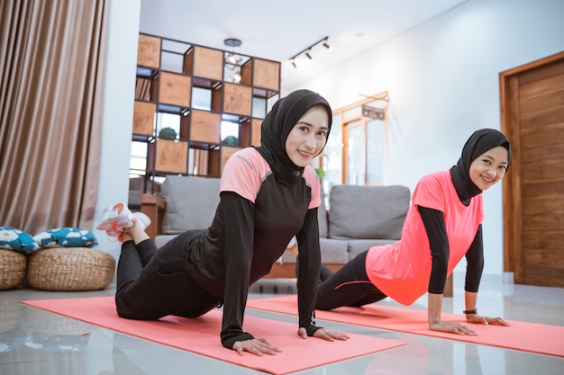 Two women wearing hijab sportswear smile while doing push ups together on a mat on the floor in the house