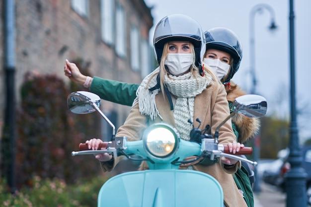 Две женщины в масках едут на скутере
