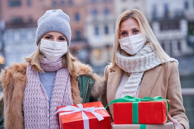 Две женщины в масках и держат рождественские подарки в городе