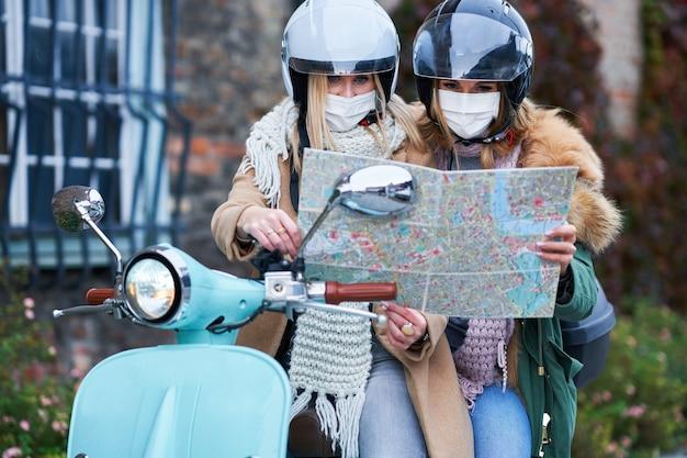 Две женщины в масках и держат карту во время поездки на скутере