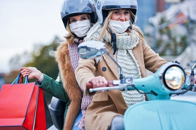 Две женщины в масках и держат сумки с покупками на скутере