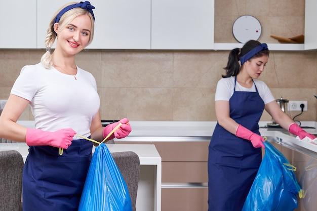 台所に立っているゴミ袋を保持している保護ゴム手袋を着用している2人の女性。クリーニングサービスのコンセプト。チームワーク
