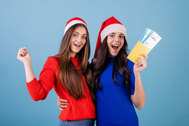 Two women wearing santa hats with airplane tickets and passport isolated over blue