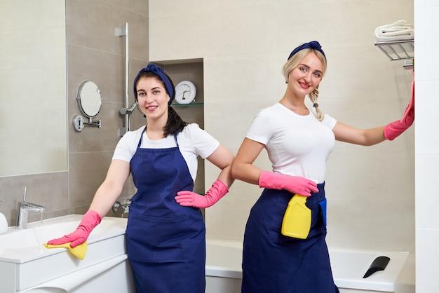 制服を着た2人の女性がバスルームに立っています。クリーニングサービスのコンセプト