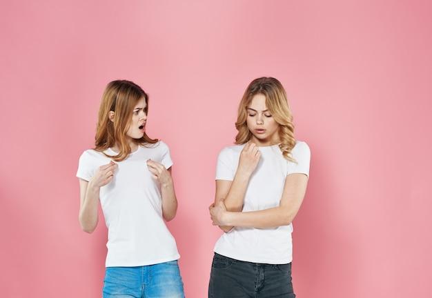 Две женщины в белых футболках на розовом фоне