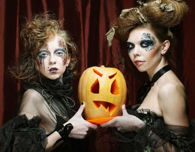 Two women with bright make up holding pumpkin