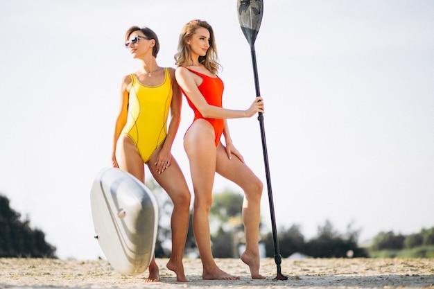 Две женщины с каноэ на пляже